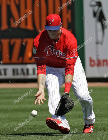 Philadelphia Phillies right fielder Michael Saunders reaches down to field a bloop single by Minnesota Twins' Eddie Rosario during the first inning of a spring training baseball game, in Clearwater, Fla