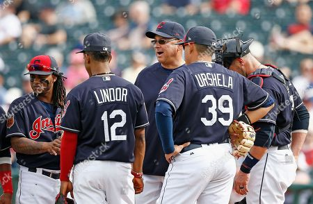 Cleveland Indians manager Terry Francona, center, waits with second baseman Michael Martinez, left, shortstop Francisco Lindor (12), third baseman Giovanny Urshela (39) and catcher Yan Gomes, right, for a new pitcher after a grand slam by Colorado Rockies' Stephen Cardullo during the fourth inning of a spring training baseball game, in Goodyear, Ariz