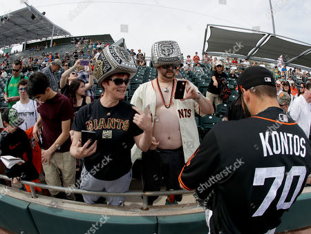 Stock Photo of Cindy Nelson, left, and Ed Sandoval wait for San Francisco Giants relief pitcher George Kontos to sign autographs before the team's spring training baseball game against the Oakland Athletics in Mesa, Ariz