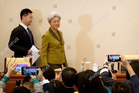 Fu Ying, right, the spokeswoman for China's National People's Congress, arrives for a press conference held at the Great Hall of the People in Beijing, . Fu said on Saturday that China will raise its defense budget by about 7 percent this year, continuing a trend of lowered growth amid a slowing economy