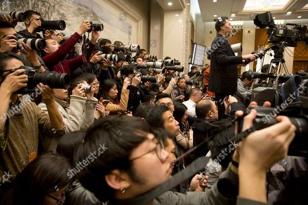 Photographers take photographs during a press conference held by Fu Ying, spokeswoman for China's National People's Congress, at the Great Hall of the People in Beijing, . Fu said on Saturday that China will raise its defense budget by about 7 percent this year, continuing a trend of lowered growth amid a slowing economy