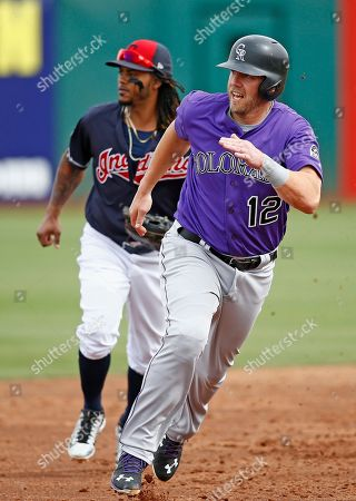 Colorado Rockies first baseman Mark Reynolds (12) rounds second base on his way to score as Cleveland Indians second baseman Michael Martinez, left, watches for the ball in the outfield during the third inning of a spring training baseball game, in Goodyear, Ariz. The Rockies defeated the Indians 16-7