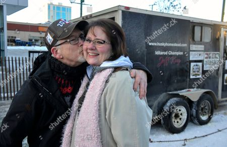 Julie Clair of Burlington, right, Kan., gets a kiss from four-time champion Jeff King prior to the ceremonial start of the Iditarod Trail Sled Dog Race in Anchorage, Alaska