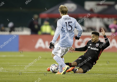 D.C. United Defender #5 Sean Franklin slides in to take the ball away from Sporting KC Defender Seth Sinovic during an MLS soccer match between the D.C. United and the Sporting KC at RFK Stadium in Washington DC