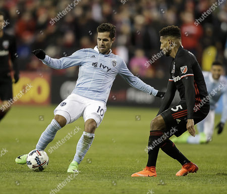 Sporting KC Midfielder Benny Feilhaber works the ball in front of D.C. United Defender #5 Sean Franklin during an MLS soccer match between the D.C. United and the Sporting KC at RFK Stadium in Washington DC. The match ends in a tie