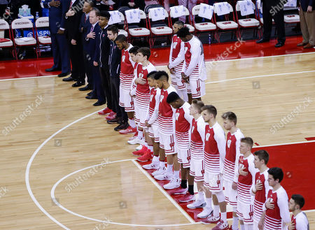 Wisconsin's Nigel Hayes, right, and Jordan Hill stand behind their teammates and coaches during the national anthem before an NCAA college basketball game against Iowa, in Madison, Wis