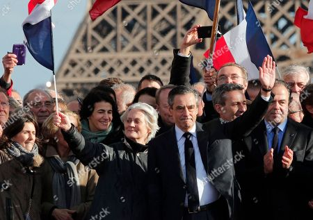 """French conservative presidential candidate Francois Fillon and his wife Penelope wave during a rally in Paris, . Fillon is urging his supporters not to """"give up the fight"""" for the presidency despite corruption allegations dogging him"""