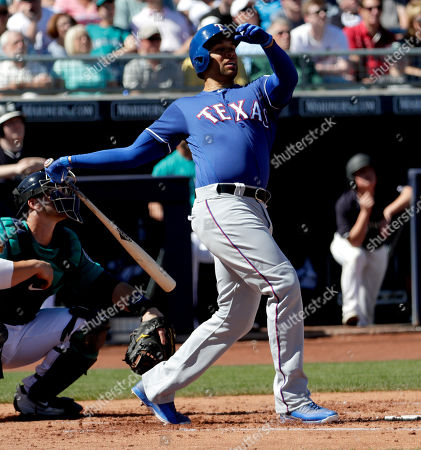 Texas Rangers' James Loney hits against the Seattle Mariners during the second inning of a spring training baseball game, in Peoria, Ariz
