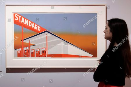 """A British Museum representative poses for photographs next to """"Standard Station"""" by Edward Ruscha which features in """"The American Dream: pop to the present"""" exhibition during a media photocall at the British Museum in London, . The exhibition, which opens to the public from March 9 and runs until June 18, charts modern and contemporary print making"""
