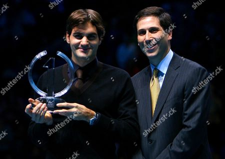 Roger Federer of Switzerland Receives the 2009 Year End No 1 Trophy From Adam Helfant Atp Executive Chairman and President at the London Atp World Tour Finals London 2009