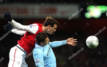Sebastien Squillaci of Arsenal in Action with Edin Dzeko of Manchester City United Kingdom London