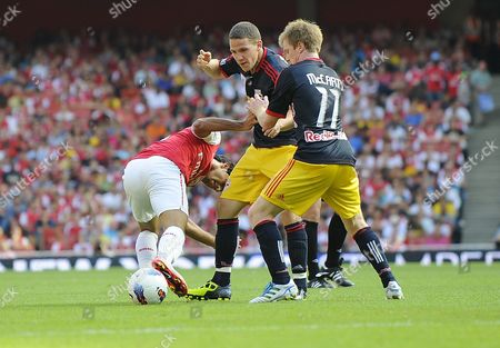 John Rooney Centre and Dax Mccarty of the New York Red Bulls Challenge Carlos Vela of Arsenal United Kingdom London