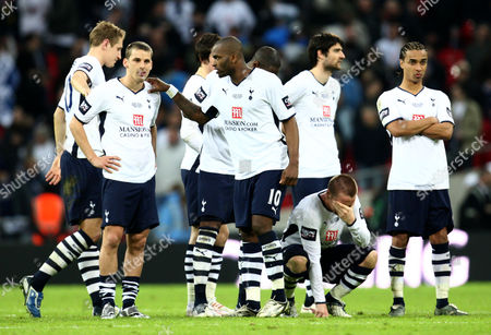 Stock Photo of Darren Bent of Tottenham Hotspur Consoles Team Mate David Bentley As Jamie O'hara (below) Squats Dejected After Missing His Attempt at Goal Aswell Giving the Carling Cup to Manchester United United Kingdom London