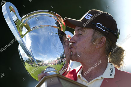 Stock Photo of Miguel Angle Jimenez of Spain Kisses the Omega European Masters Trophy and Wears the Winners Red Jacket