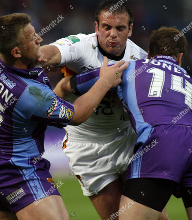 Andy Lynch of Bradford Bulls battles his way through Keith Mason and Stuart Jones of Huddersfield Giants