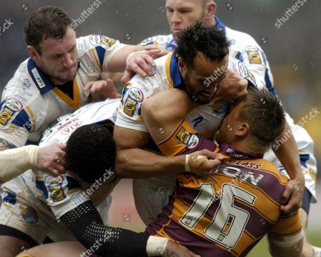 Jamie Jones-Buchanan and team mates of Leeds Rhinos tackle Keith Mason of Huddersfield Giants