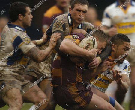 Kevin Sinfield and Clinton Toopi of Leeds Rhinos tackle Keith Mason of Huddersfield Giants