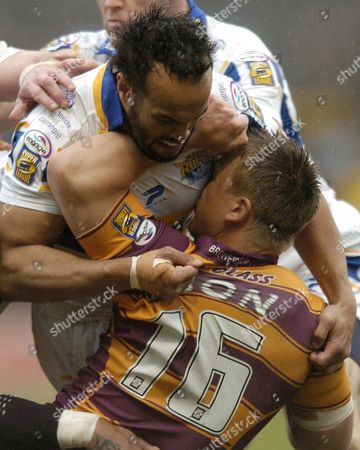 Jamie Jones-Buchanan of Leeds Rhinos tackles Keith Mason of Huddersfield Giants