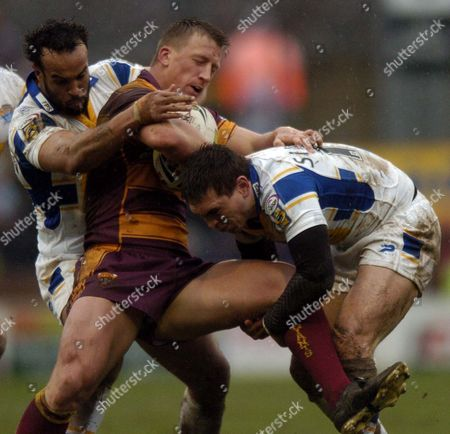 Jamie Jones-Buchanan and Gary Sinfield of Leeds Rhinos tackle Keith Mason of Huddersfield Giants