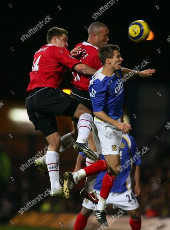 Portsmouth's Gary O'Neill and Manchester United's Alan Smith and Mikael Sylvestre all jump for the header