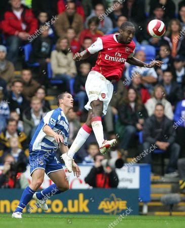 Johann Djourou of Arsenal heads clear as Shane Long of Reading looks on
