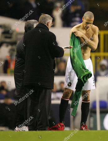 Rio Ferdinand of Manchester United starts to put on a goalkeepers shirt after Edwin van der Saar was injured