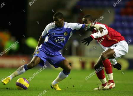 Henri Camara of Wigan Athletic turns away from Johann Djourou of Arsenal