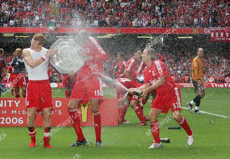 Boudewijn Zenden sprays champagne on Liverpool scorers John Arne Riise, left and Peter Crouch