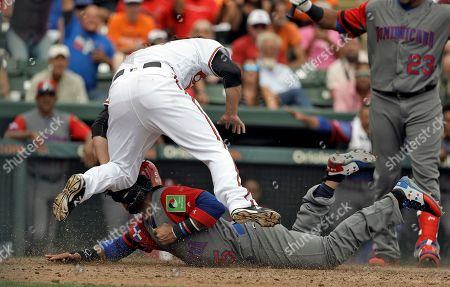 Jonathan Vallar, Zach Stewart Baltimore Orioles pitcher Zach Stewart (50) goes airborne as he attempt to tag out Dominican Republic infielder Jonathan Villar (5) at home plate during the sixth inning of a exhibition baseball game, in Sarasota, Fla. Villar scored on a wild pitch by Stewart