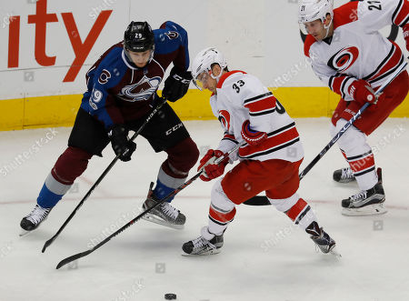 Nathan MacKinnon, Derek Ryan, Lee Stempniak Carolina Hurricanes center Derek Ryan, front, battles to control the puck with Colorado Avalanche center Nathan MacKinnon, back, as Hurricanes right wing Lee Stempniak follows the play in the third period of an NHL hockey game, in Denver. The Avalanche won 3-1