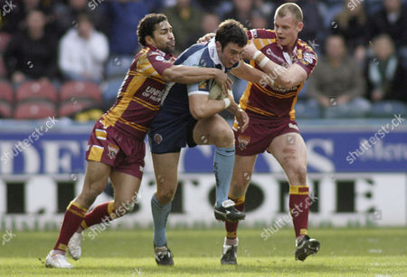 Kirk Dixon of Castleford Tigers is tackled by Rod Jensen and Kevin Brown of Huddersfield Giants