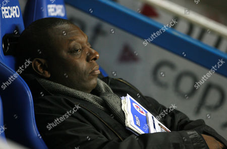 BBC reporter Garth Crooks lounges in the Reading dugout before the match