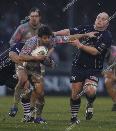 Jerome Fillol of Srade Francais hands off Jason Hobson of Bristol Rugby