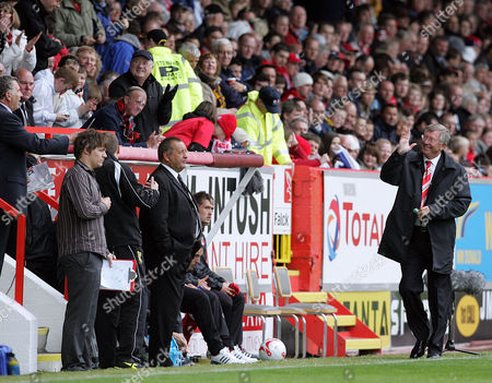 Manager Sir Alex Ferguson of Manchester United is recieved warmly after half time at Aberdeen as he waves to the directors box, in front of  Jimmy Calderwood, manager of Aberdeen