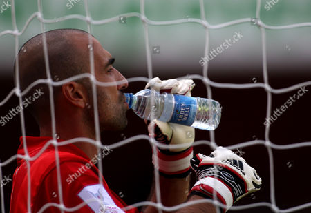 Stock Photo of Paris St Germain goalkeeper Jerome Alonzo drinks some Abbey Well mineral water in his goal