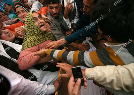 Relatives Wail Near the Open Coffin of Haji Syed Mohammad Yousuf who Allegedly Died in Police Custody During His Funeral in Locktipora Some 55 Kilometers South of Srinagar the Summer Capital Indian Kashmir 01 October 2011 Haji Syed Mohammad Yousuf a 61-year-old Retired Teacher and National Conference (nc) Party Worker Allegedly Died in Police Custody on 30 September After the Disputed Region's Top Senior (nc) Minister Handed Him Over to Investigators For His Alleged Involvement in a Bribery Case India Srinagar
