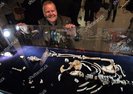Us Professor Lee Berger Poses For Photographs with the Fossilized Skeleton of Australopithcus Sediba at the University of the Witwatersrand in Johannesburg South Africa 08 September 2011 Berger and His Nine-year-old Son Matthew Discovered the Fossils at a Site at Malapa North of Johannesburg in 2008 a Close Examination of Two Partial Fossilized Skeletons of a Sediba Suggests These Creatures who Roamed the Earth Some 1 9 Million Years Ago Were Crafting Tools Even Earlier and Could Be the First Direct Ancestor of the Homo (human) Species Based on the Most Complete Hand Specimen Ever Found a Sediba Had an Extra-long Thumb and Powerful Fingers Which It Could Have Used to Make Tools Despite Still Having a Small Ape-like Brain Suggested Findings by Berger's Team Published in the Journal Science South Africa Johannesburg