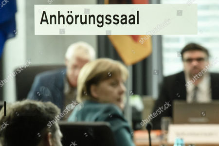German Chancellor Angela Merkel (C) attends a parliamentary commission investigating the diesel emissions scandal involving German carmaker Volkswagen (VW), in Berlin, Germany, 08 March 2017. New evidence suggests that former CEO of VW, Martin Winterkorn knew earlier than he claims about fraudulent emission tests in Volkswagen vehicles. The writing on the window reads 'Hearing hall'.