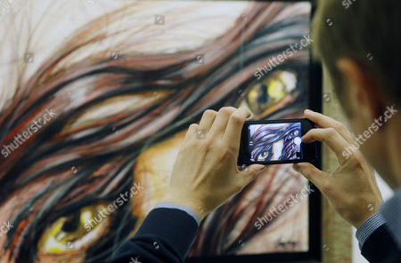 Stock Photo of Visitor Takes a Picture of an Art Works of Father's of the Former French President Nicholas Sarkozy Pal Sarkozy Sduring Opening of His Exhibition in the Russia's Fine Art Exhibition Hall in Moscow 01 September 2015 Hungarian Born Pal Sarkozy 88 Arrived in France in 1948 and Made a Carrier of Successful Designer Designer and Started As an Artist Only in 2001 Russian Federation Moscow