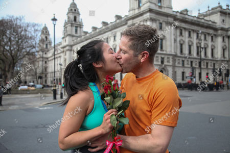 Stock Photo of Eric Lohela and Elizabeth Wang from San Francisco kissing outside Parliament after receiving red roses