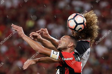 Rever of Brazil's Flamengo, front, fights for the ball with Fabricio Coloccini of Argentina's San Lorenzo during a Copa Libertadores soccer match at Maracana stadium in Rio de Janeiro, Brazil