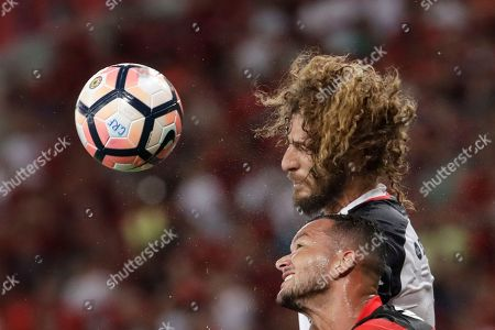 Rever, of Brazil's Flamengo, bottom, fights for the ball with Fabricio Coloccini, of Argentina's San Lorenzo, during a Copa Libertadores soccer match at Maracana stadium in Rio de Janeiro, Brazil