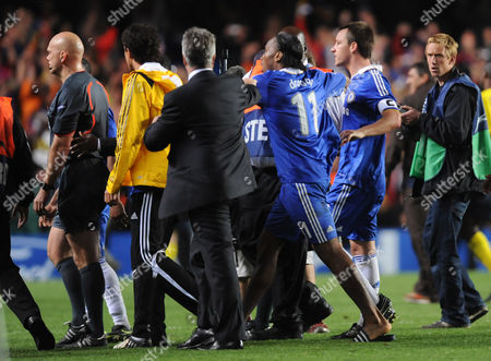Chelsea Manager Guus Hiddink Tries to Stop His Players Including Didier Drogba and John Terry From Confronting Referee Tom Henning Ovrebo at Full Time United Kingdom London