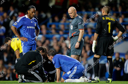 Didier Drogba Referee Tom Henning Ovrebo and Victor Valdes of Barcelona Look On As Frank Lampard of Chelsea Receives Medical Treatment United Kingdom London