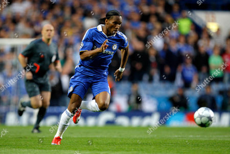Didier Drogba of Chelsea Chases the Ball with Referee Tom Henning Ovrebo Looking On in the Distance United Kingdom London