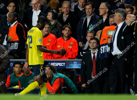 A Dejected Eric Abidal of Barcelona Walks Past Team Mates After Being Sent Off by Referee Tom Henning Ovrebo Chelsea Manager Guus Hiddink Looks On United Kingdom London