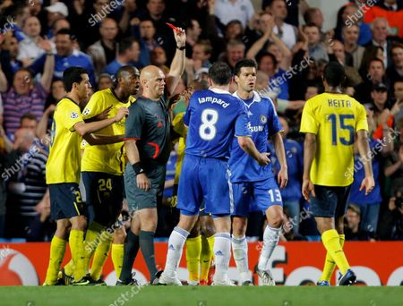 Stock Photo of Barcelona Players Surround Referee Tom Henning Ovrebo As He Issues A Red Card to Eric Abidal of Barcelona For A Foul On Nicolas Anelka of Chelsea United Kingdom London