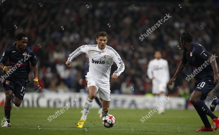 Cristiano Ronaldo of Real Madrid Chased by Jean Ii Makoun (left) and Aly Cissokho (right) of Olympique Lyonnais Spain Madrid