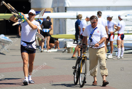 Great Britain head rowing coach Jurgen Grobler walks beside Peter Reed who carries the blades