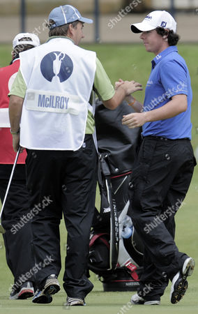 Rory Mcilroy of Northern Ireland Shakes Hands with Caddie J P Fitzgerald On the 18th Green and Leads the Open Championship On -9 Under Par A Course Record 63 United Kingdom Fife